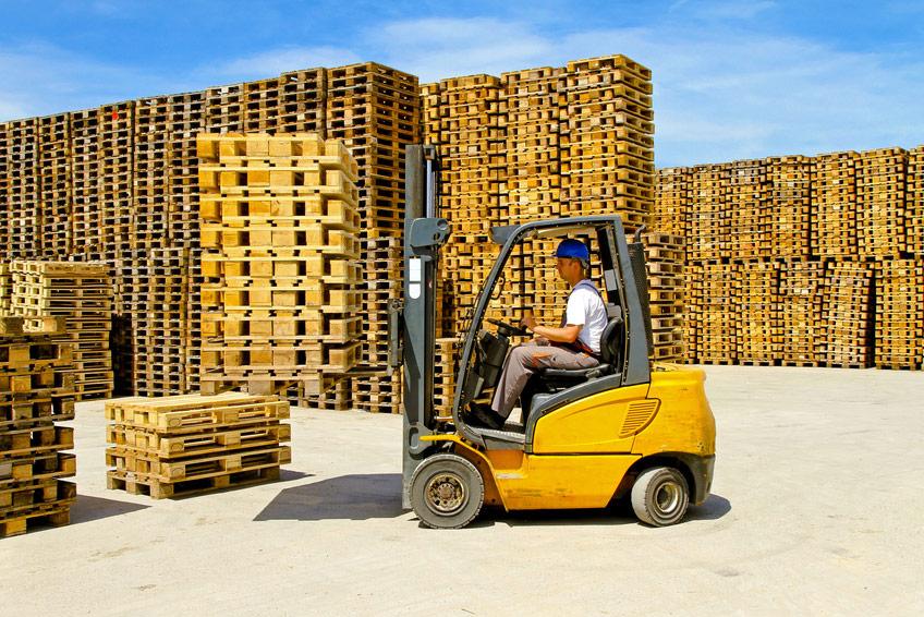 Pracownik transportujący palety wózkiem widłowym